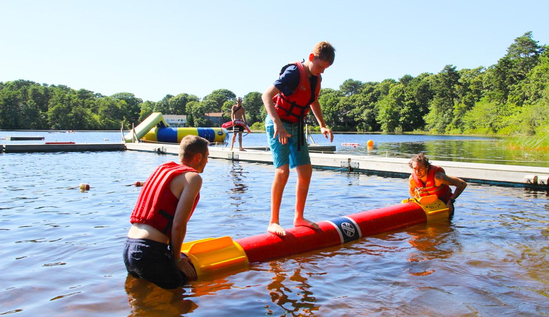 Kids balancing on a log in the lake