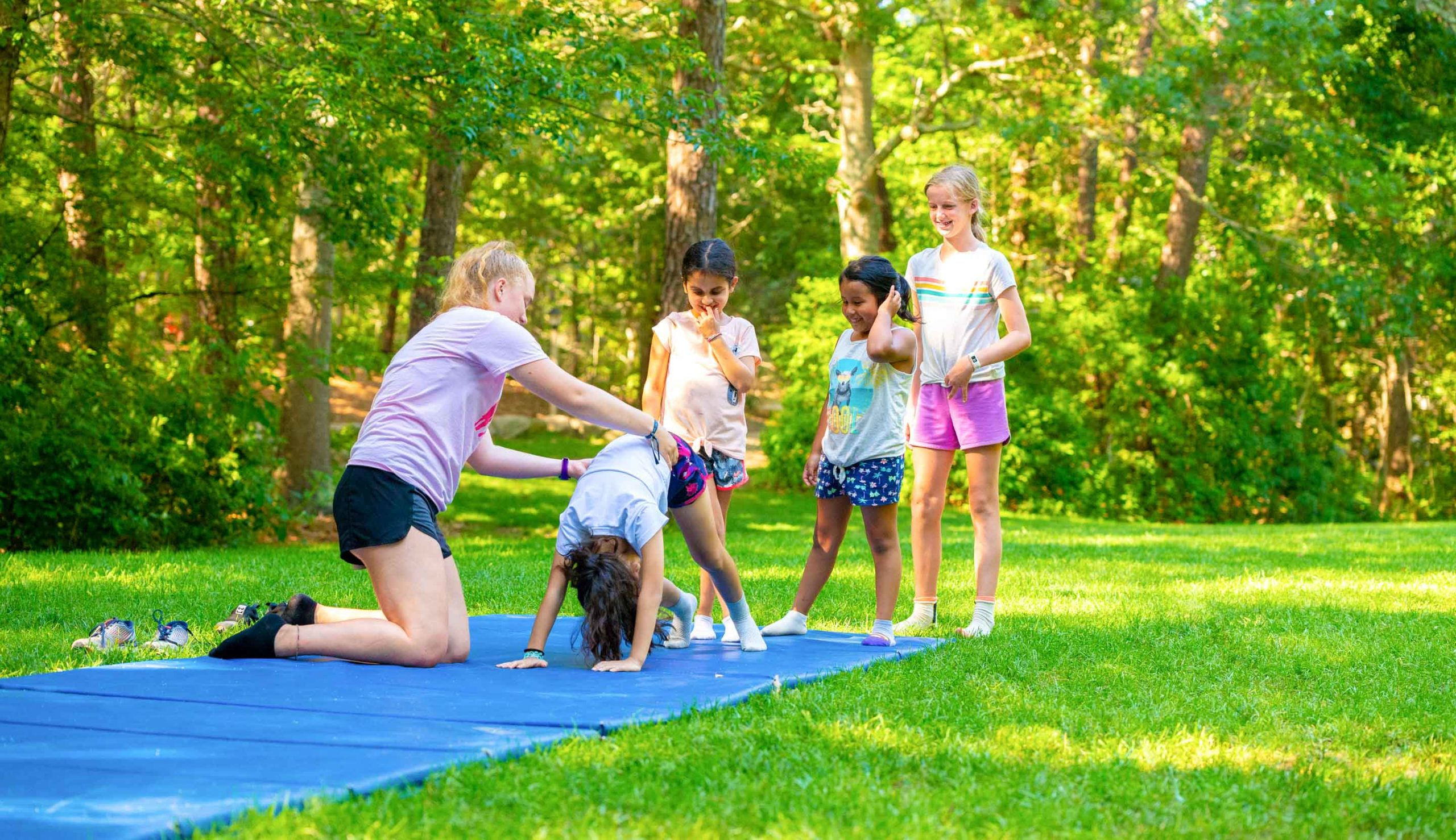 Young campers doing gymnastics outside
