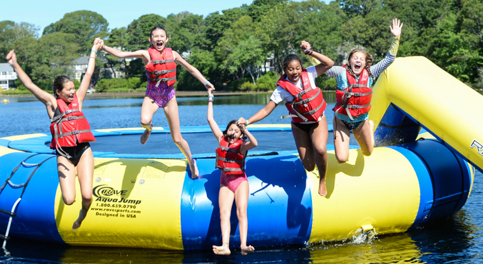 Kids holding hands jumping off of the water trampoline into the lake