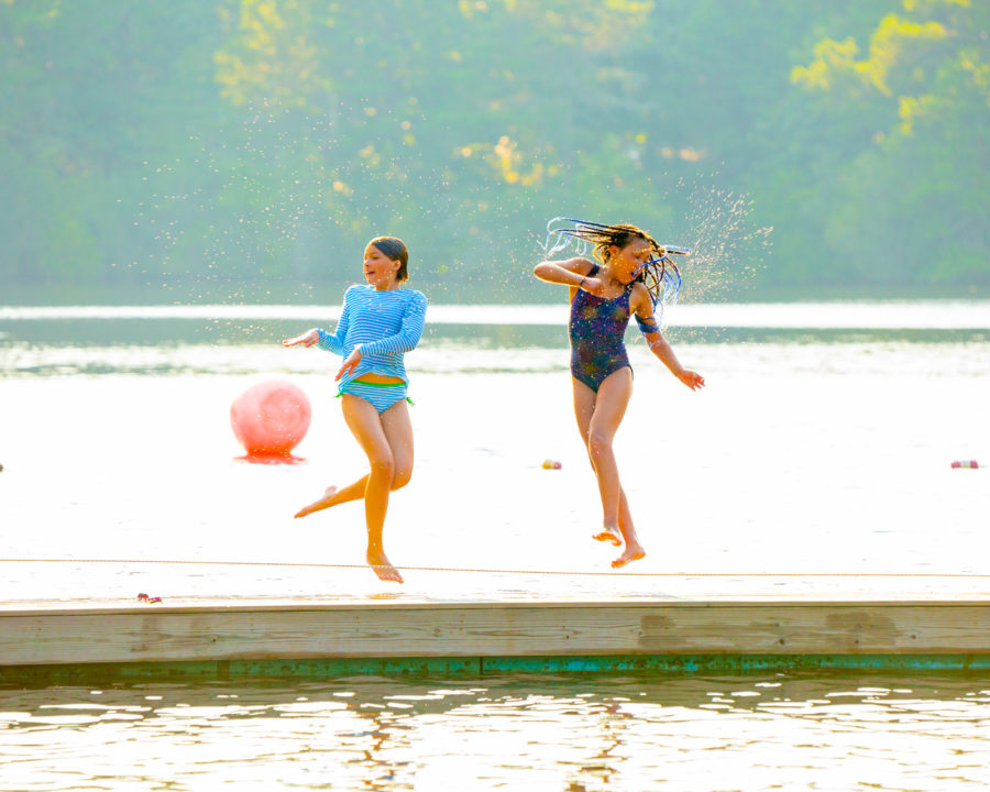 Campers jumping and spinning on the dock