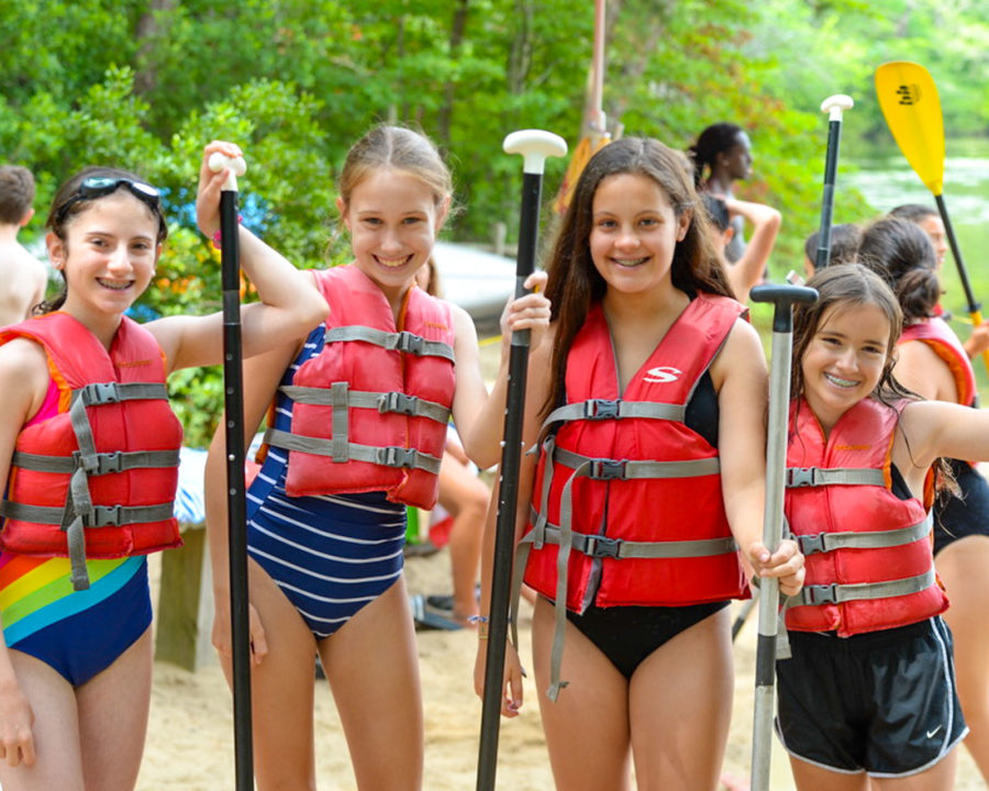 Girls in life vests holding kayak paddles